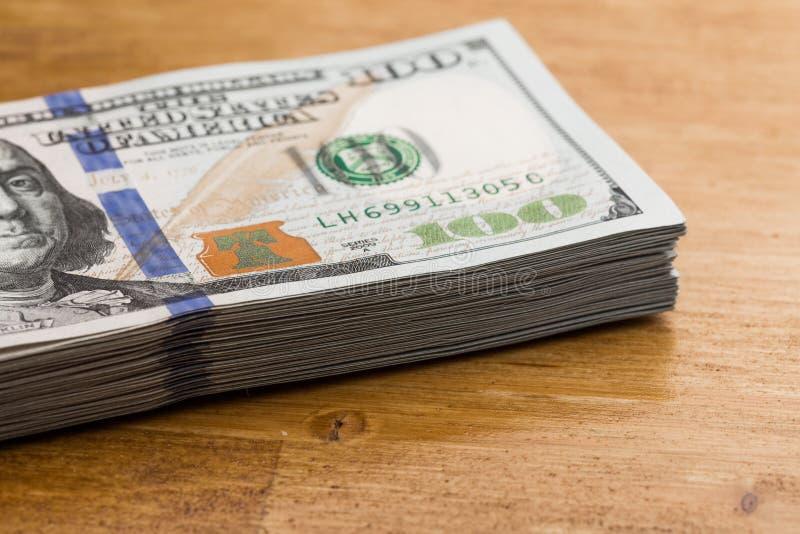 Pile de cent billets d'un dollar sur une table en bois photos libres de droits