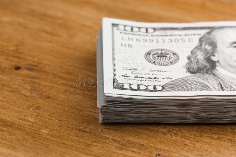 Pile de cent billets d'un dollar sur une table en bois photographie stock libre de droits