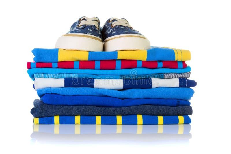 Pile de chemises colorées d'été et une paire d'espadrilles sur le principal i image stock