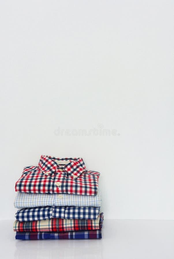Pile de chemises de plaid sur le fond blanc photo stock