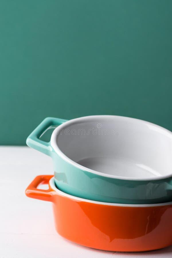 Pile de cocottes en céramique d'orange et de turquoise sur le fond en bois blanc de mur de vert de table Cuisson du concept de cu photos stock