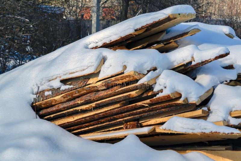 pile de conseils sciés couverts dans la neige image libre de droits