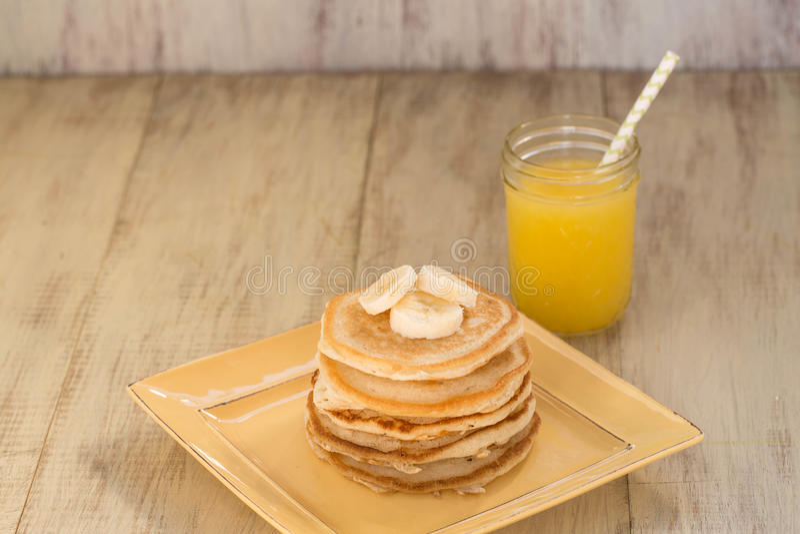 Pile de crêpes avec les bananes et le jus d'orange frais photographie stock