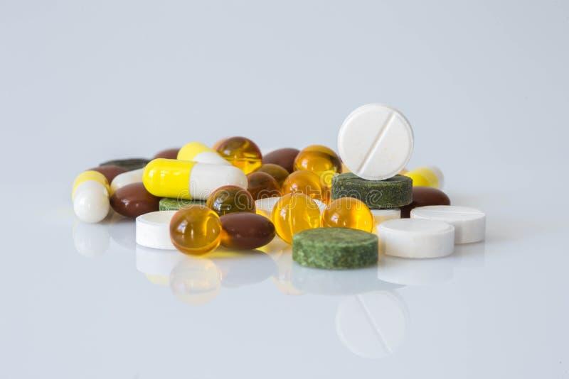 Pile de diverses pilules colorées d'isolement sur le blanc images stock