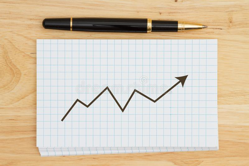 Pile de fiches blanches vierges de graphique sur le bureau en bois avec un stylo a images stock