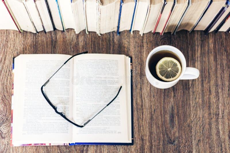 Pile de fond d'éducation de livres, de livre ouvert, de verres, et de tasse de thé avec le citron photos stock