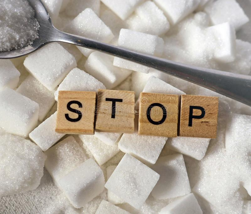 Pile de H des cubes en sucre blanc et arrêter le mot dans les caractères gras comme donnent un avis sur des calories de dépendanc photo libre de droits