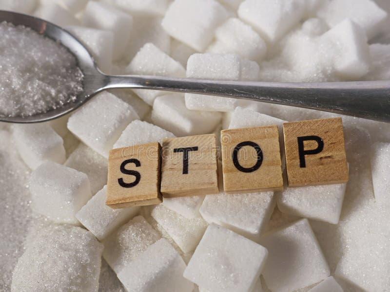 Pile de H des cubes en sucre blanc et arrêter le mot dans les caractères gras comme donnent un avis sur des calories de dépendanc image libre de droits