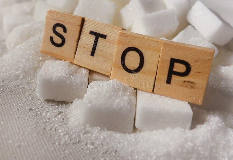 Pile de H des cubes en sucre blanc et arrêter le mot dans les caractères gras comme donnent un avis sur des calories de dépendanc images stock