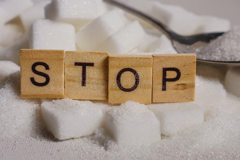Pile de H des cubes en sucre blanc et arrêter le mot dans les caractères gras comme donnent un avis sur des calories de dépendanc photos stock