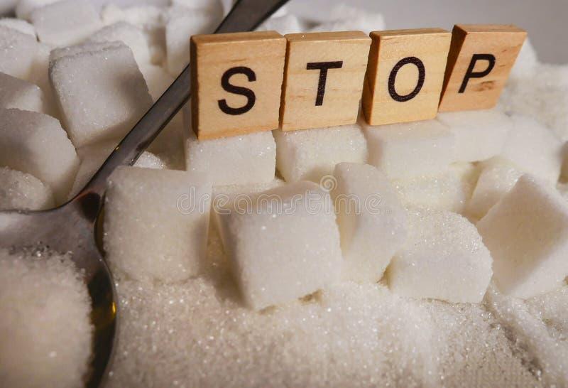 Pile de H des cubes en sucre blanc et arrêter le mot dans les caractères gras comme donnent un avis sur des calories de dépendanc photo stock