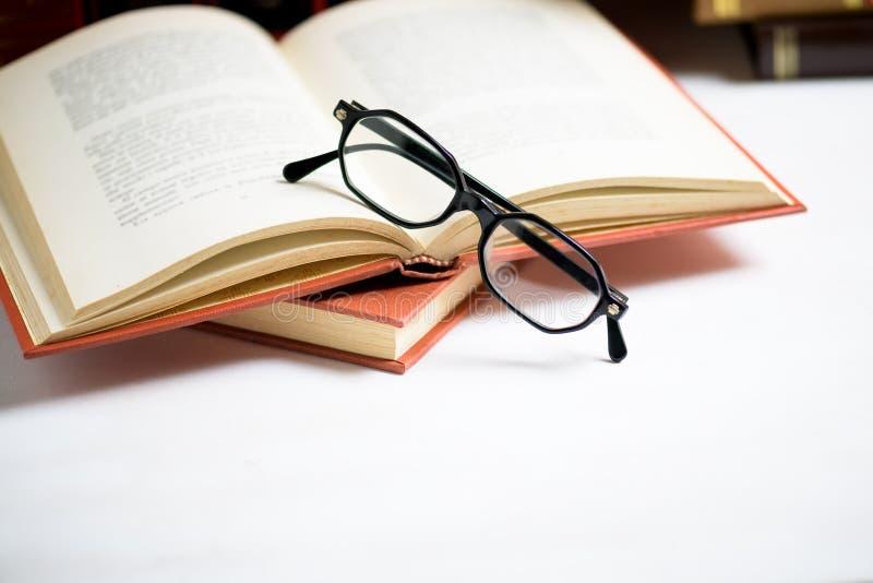 Pile de livres avec des verres placés sur le livre ouvert dans la bibliothèque image libre de droits