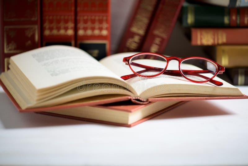 Pile de livres avec les verres rouges placés sur le livre ouvert dans la bibliothèque photo stock