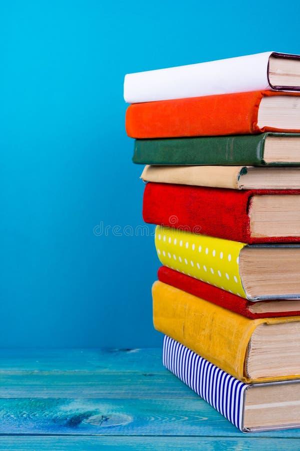 Pile de livres colorés, fond bleu sale, l'espace d'exemplaire gratuit photographie stock