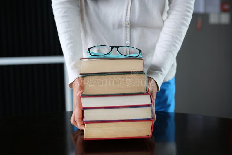 Pile de livres de livre cartonné chez des mains de la femme photos libres de droits