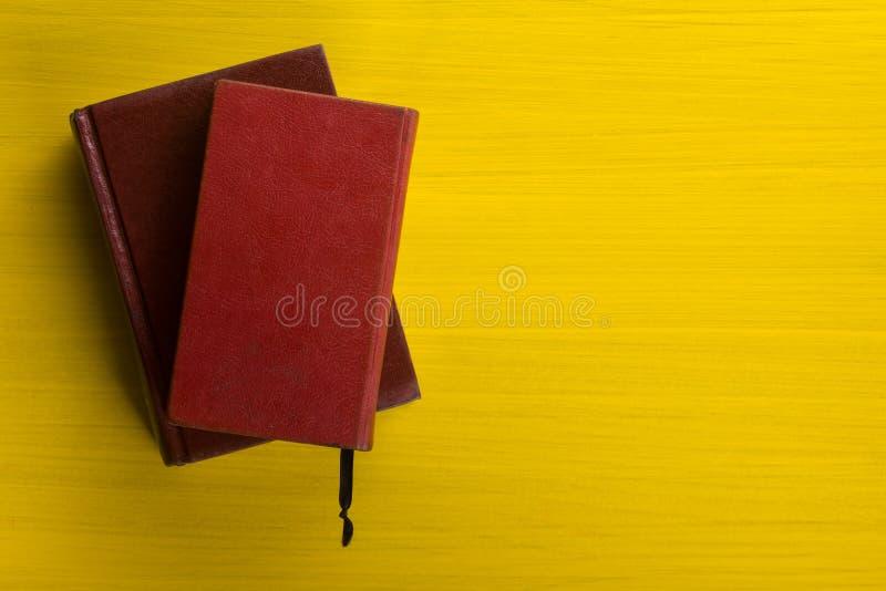Pile de livres de livre cartonné, de journal intime sur la table en bois de plate-forme et de fond jaune De nouveau à l'école Cop photos stock