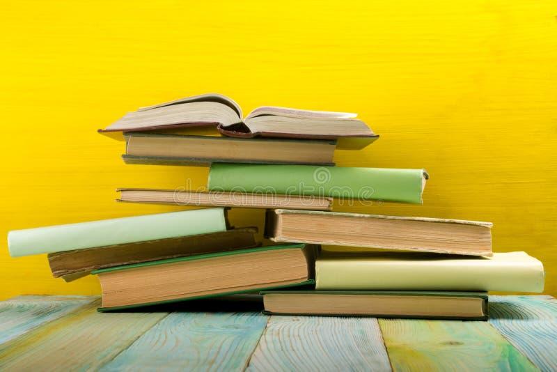Pile de livres de livre cartonné, de journal intime sur la table en bois de plate-forme et de fond jaune De nouveau à l'école Cop images stock