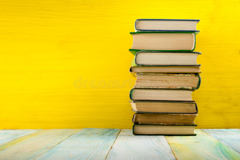 Pile de livres de livre cartonné, de journal intime sur la table en bois de plate-forme et de fond jaune De nouveau à l'école Cop photographie stock