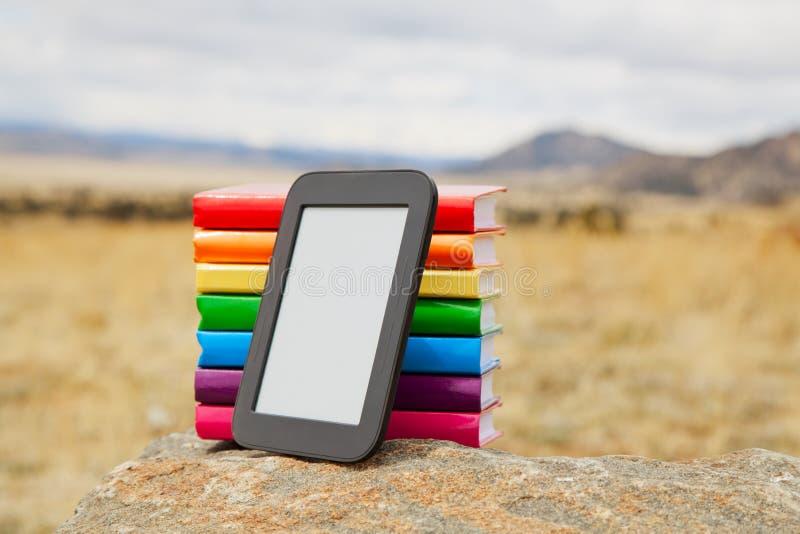 Pile de livres estampés avec le lecteur électronique de livre photographie stock libre de droits
