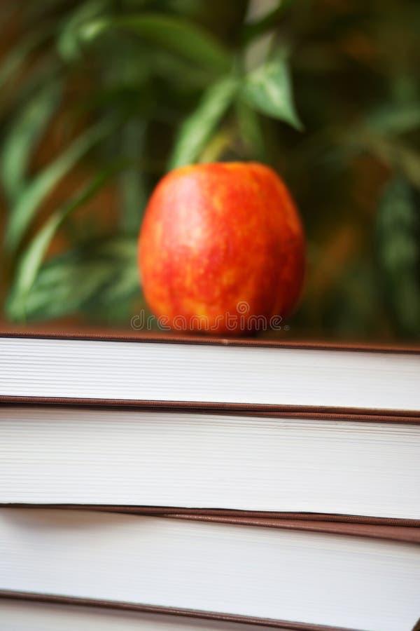Pile de livres sur la table en bois pour lire avec AP red delicious image libre de droits
