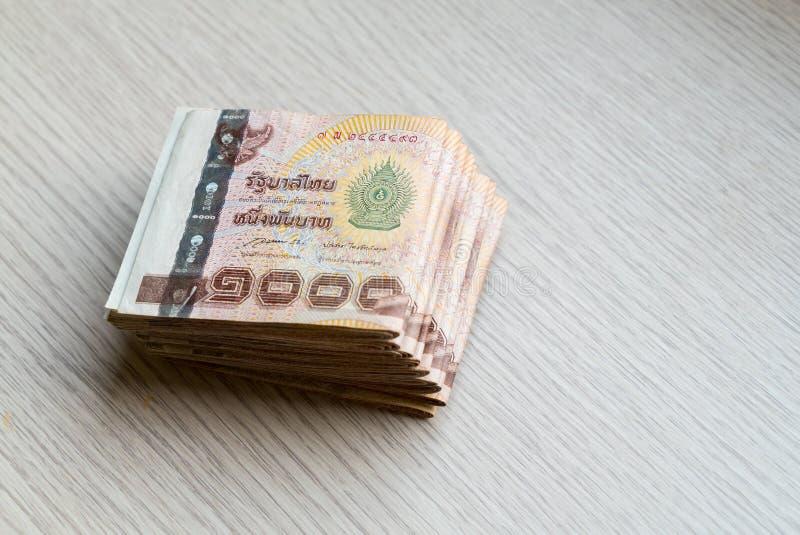 Pile de mille argents thaïlandais de bain sur la table en bois photographie stock libre de droits