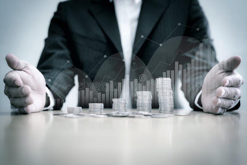Pile de participation d'homme d'affaires de pièces de monnaie sur la table avec le fond de filtre de graphique et de cru images stock