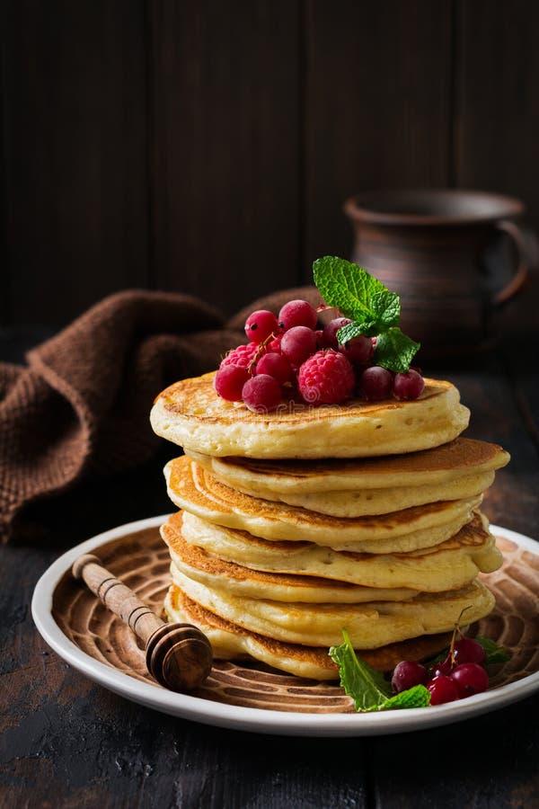 Pile de petites cr?pes faites maison avec du miel, les framboises fra?ches et les groseilles rouges sur un vieux fond en bois photo stock