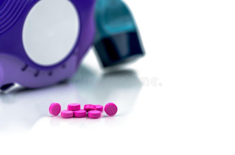 Pile de petites pilules roses rondes de comprimés sur le fond brouillé de l'inhalateur d'asthme un accuhaler photos stock