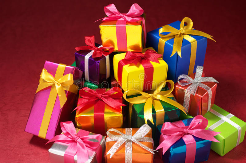 Pile de petits cadeaux sur le fond rouge. photo stock