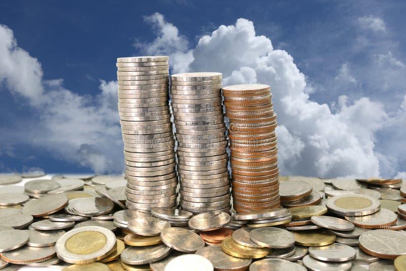 pile de pièce de monnaie sur le ciel bleu images stock