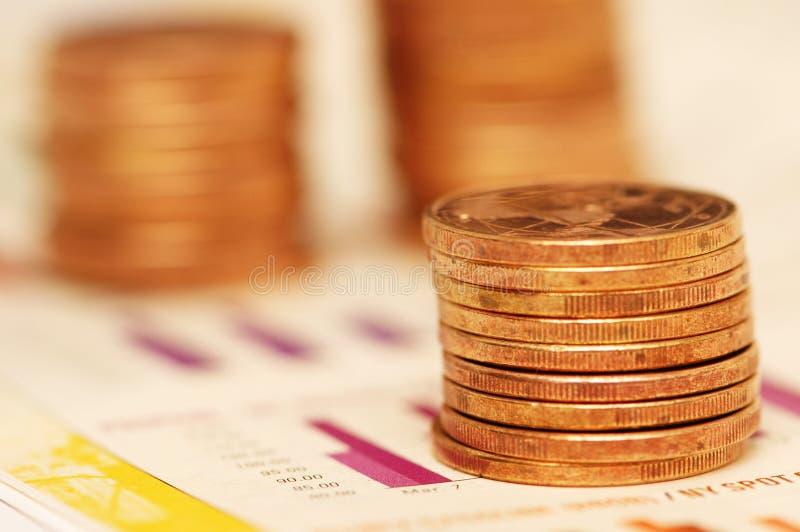 Pile de pièces de monnaie au-dessus des diagrammes à barres photos libres de droits