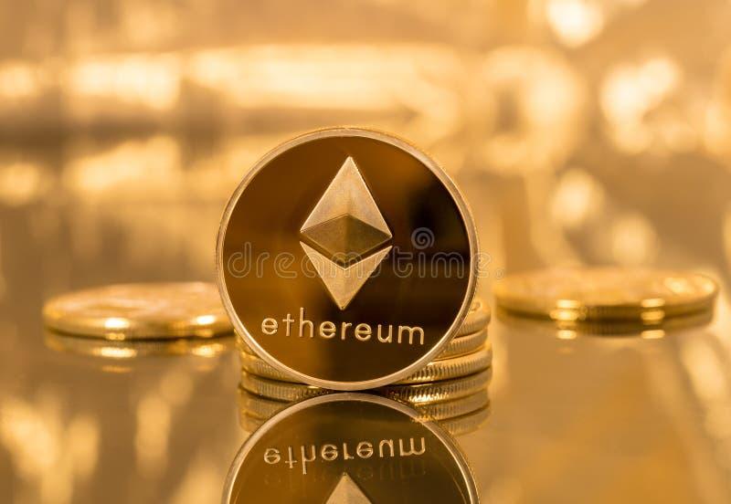 Pile de pièces de monnaie d'ethereum avec le fond d'or photographie stock libre de droits