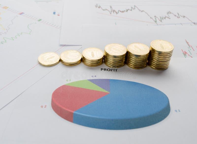 Pile de pièces de monnaie et de diagrammes financiers image libre de droits