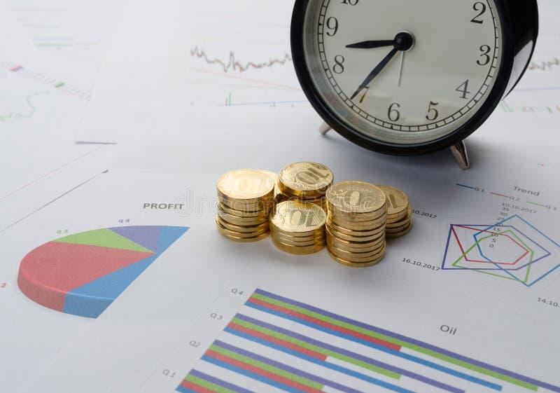 Pile de pièces de monnaie, de réveil et de diagrammes financiers image libre de droits