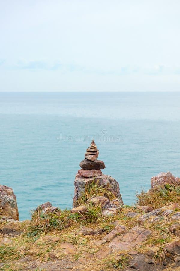 Pile de pierre d'équilibre sur le cliffside avec le fond de paysage marin photo stock