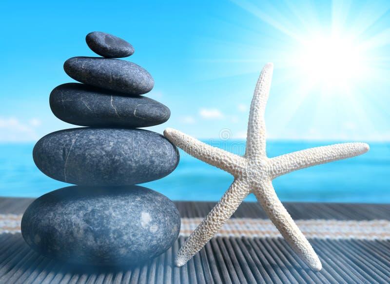 Pile de pierres de caillou de zen avec des étoiles de mer sur la plage photographie stock