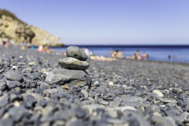 Pile de pierres de station thermale de zen sur la plage de gravier de volcan de Mavra Volia images stock