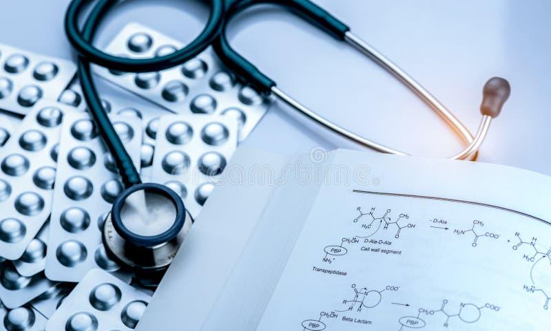 Pile de pilule de comprimés dans le habillage transparent avec le livre et le stéthoscope de structure de drogue sur le fond blan photographie stock libre de droits