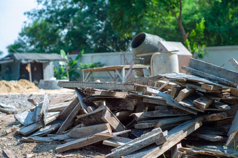 Pile de plan rapproché de bois inutile au chantier de construction avec le mélangeur concret brouillé à l'arrière-plan image stock
