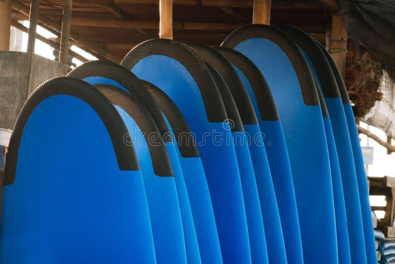Pile de planches de surf molles de couleur bleue dans une pile par l'océan bali l'indonésie Panneaux de ressac sur la plage sablo image libre de droits