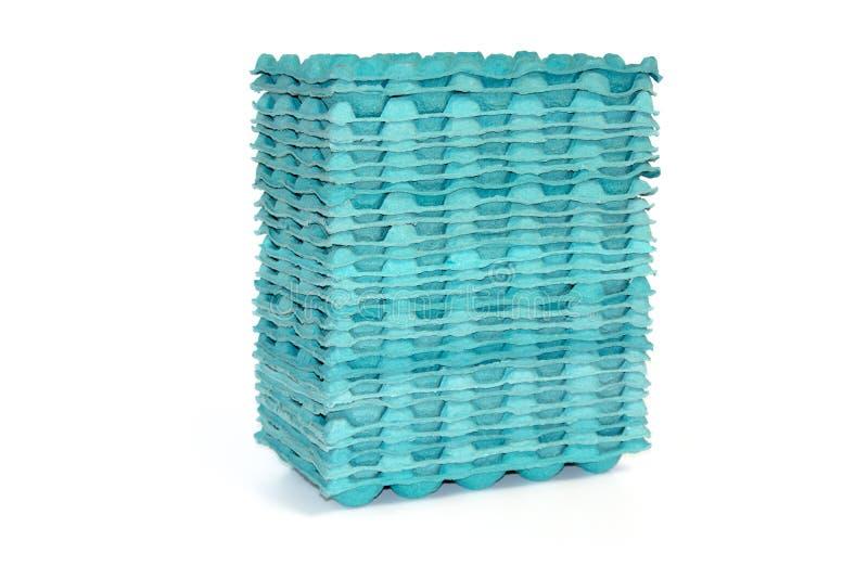 Pile de plateaux bleus d'oeufs sur un fond blanc images stock