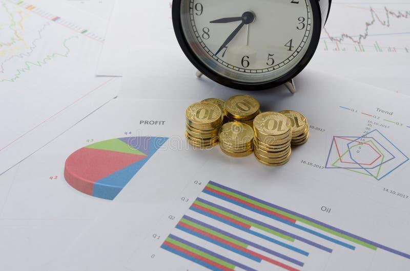 Pile de réveil de pièces de monnaie et de diagramme financier photo libre de droits