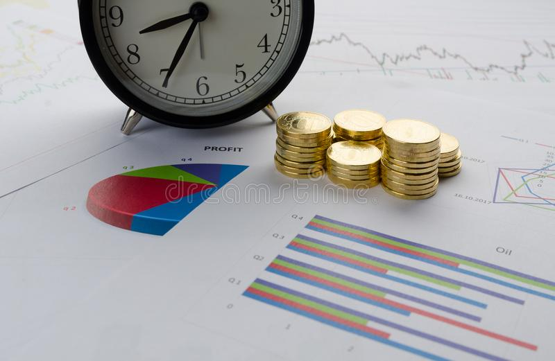 Pile de réveil de pièces de monnaie et de diagrammes financiers image stock