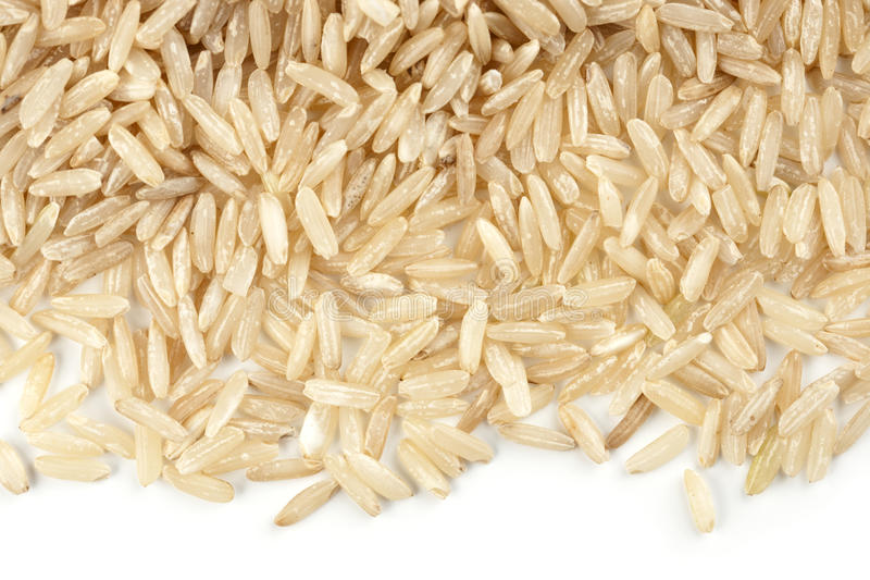 Pile de riz brun d'isolement sur le blanc photo stock