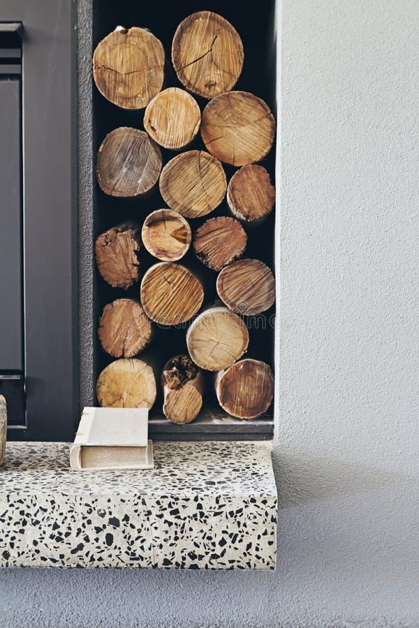Pile de rondins de bois de chauffage à côté de cheminée dans la maison contemporaine image libre de droits