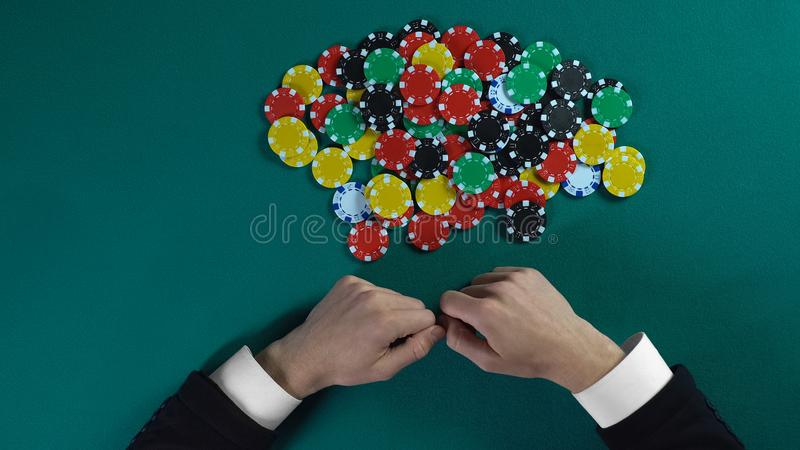Pile de saisie de gagnant des puces après jeu de poker, homme avide prenant tout l'argent photos libres de droits