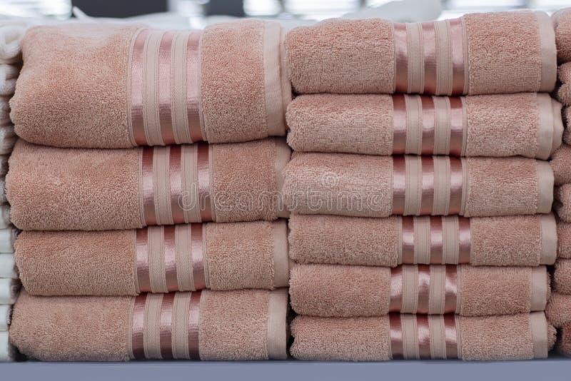 Pile de serviettes éponge roses avec une bande, une serviette propre sur l'étagère photos stock