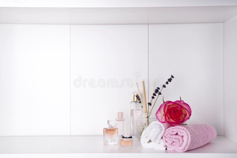 Pile de serviettes de bain avec rose et de parfums sur le fond clair photo libre de droits