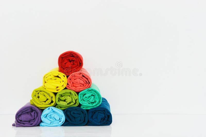 Pile de T-shirt coloré roulée sur le fond blanc image stock