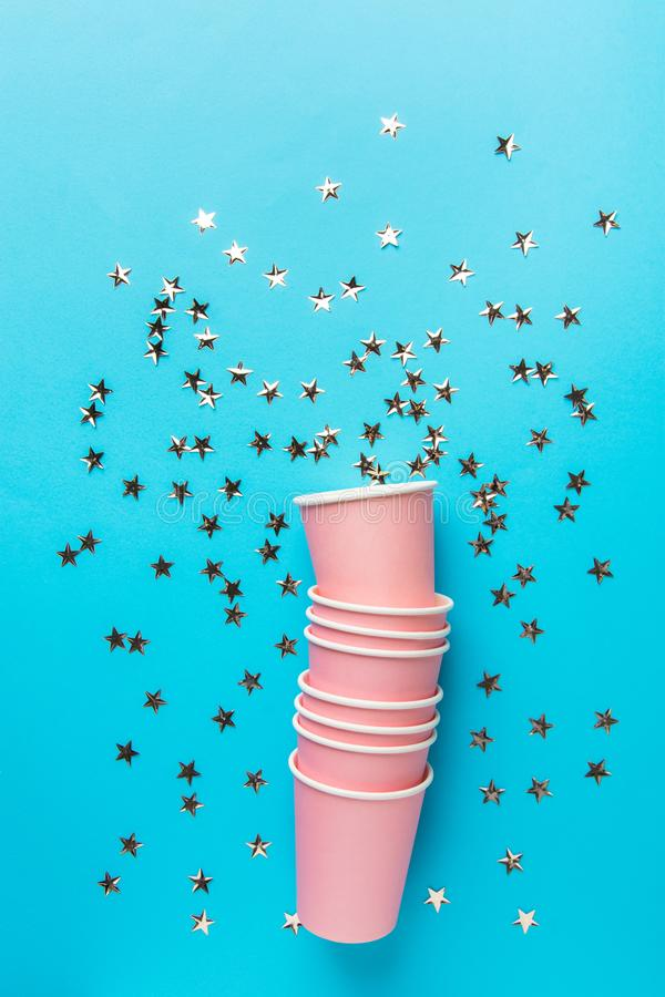 Pile de tasses de papier potables roses sur les confettis éclatants de forme d'étoile de fond bleu en bon état Enfants de vacance photo libre de droits